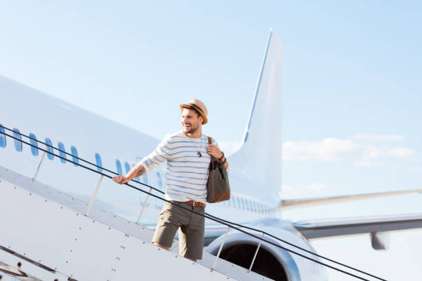 Handsome man boarding a flight stock photo