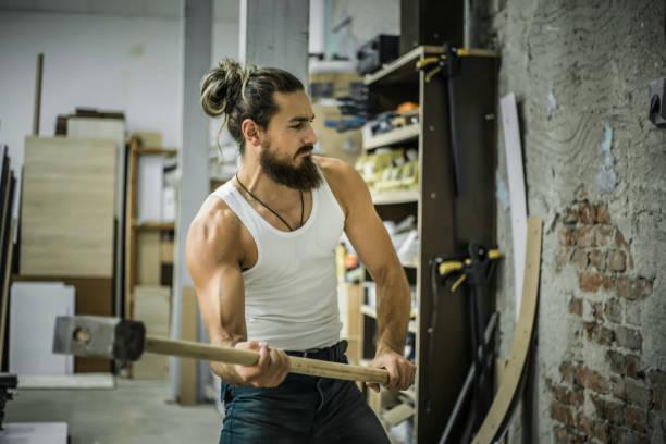 handsome man breaks a wall with a hammer - greve imagens e fotografias de stock