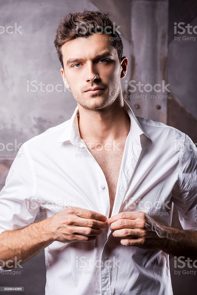 Handsome man buttoning shirt. stock photo