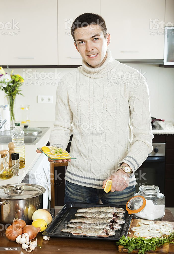 Handsome man cooking trout fish with lemon royalty-free stock photo
