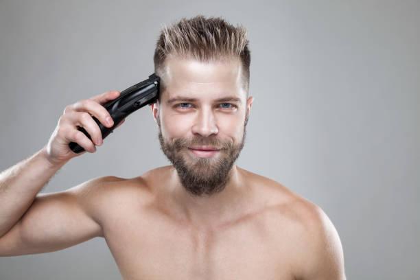 Gut aussehender Mann seine eigenen Haare mit einem Haarschneider schneiden – Foto