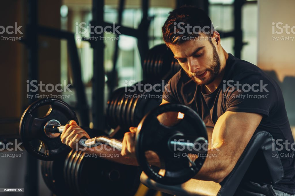 Handsome man doing biceps lifting barbell on bench in a gym stock photo