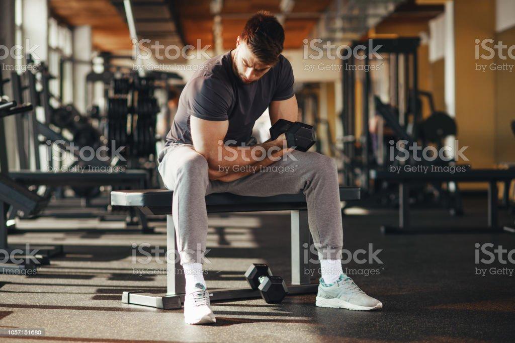Gut aussehender Mann tun Bizeps heben Hanteln auf Bank in einem Fitnessstudio – Foto