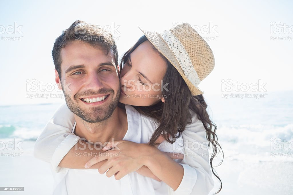 Handsome man doing piggy-back to his girlfriend stock photo