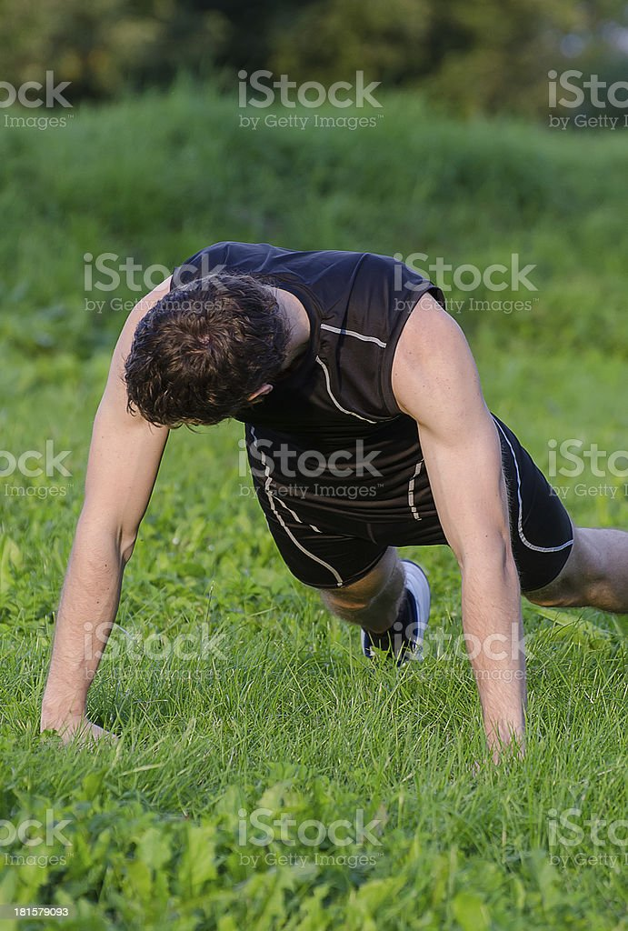 Handsome man doing push-ups at the park royalty-free stock photo