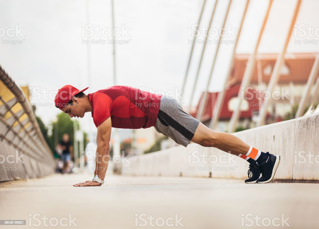 Handsome man doing push-ups outdoors on sunny day. Fitness concept royalty-free stock photo