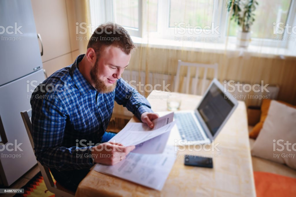 Handsome man doing some paperwork at home stock photo