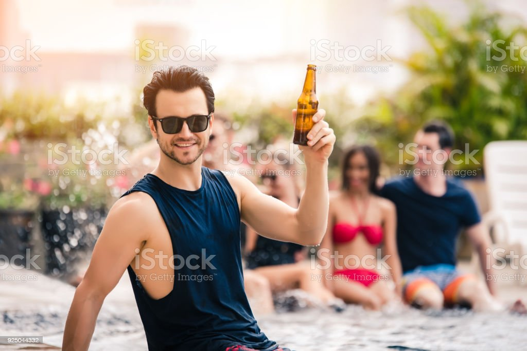 Handsome Man Drinking Beer in the Pool Party in an Evening -...