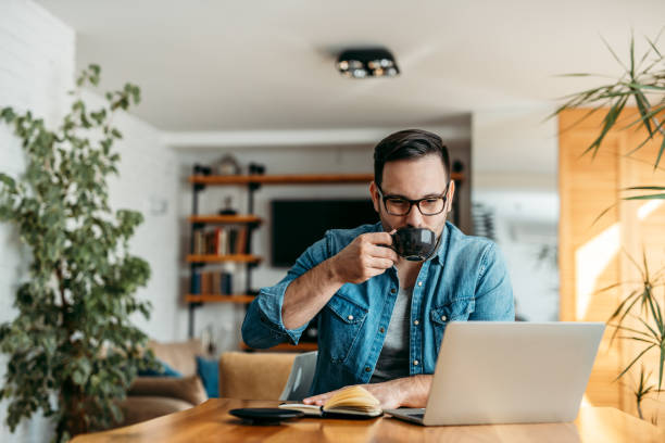 Hombre guapo bebiendo una taza de café y mirando la computadora portátil en la oficina en casa, retrato. - foto de stock