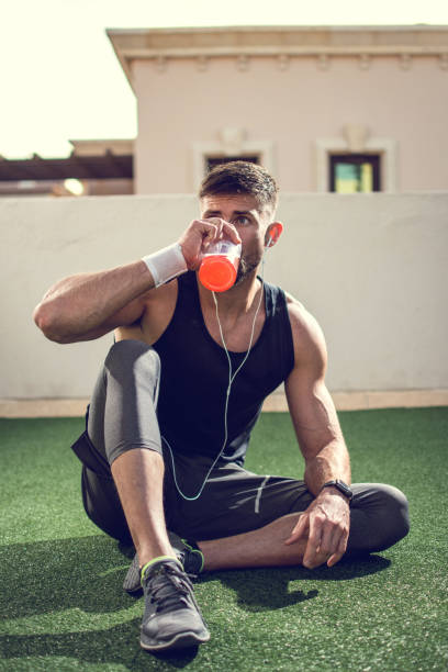 Handsome man drinking energy drink after sports training outdoors stock photo