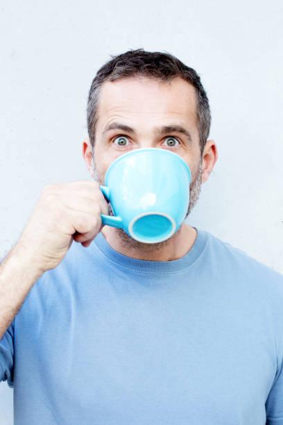gut aussehender mann aus blauen tasse trinken - gesichtertassen stock-fotos und bilder