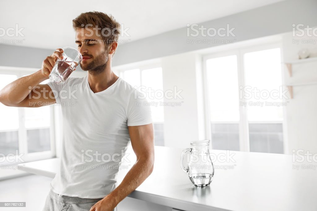 c06928414c24 Handsome Man Drinking Glass Of Fresh Water Indoors In Morning royalty-free  stock photo