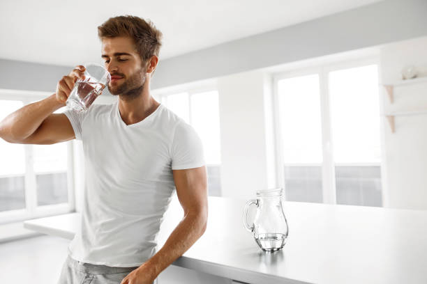Handsome Man Drinking Glass Of Fresh Water Indoors In Morning stock photo