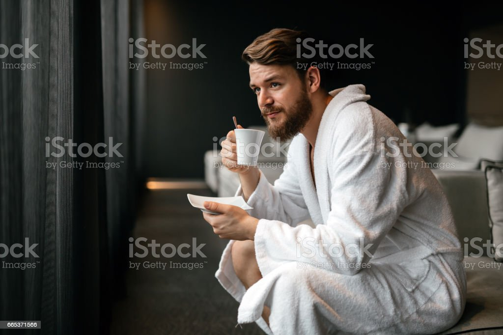Handsome man drinking tea and relaxing in bathrobe stock photo