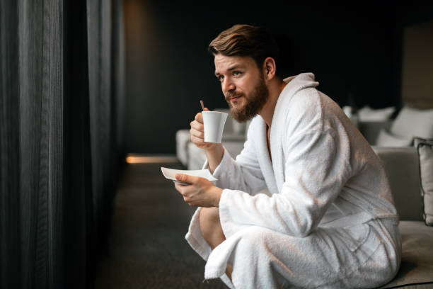 handsome man drinking tea and relaxing in bathrobe - accappatoio foto e immagini stock