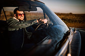 Young handsome man siting in car and driving alone in sunset, photo is taken in car from 1980 year