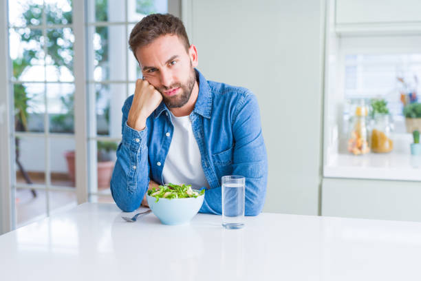 handsome man eating fresh healthy salad thinking looking tired and bored with depression problems with crossed arms. - slow food foto e immagini stock