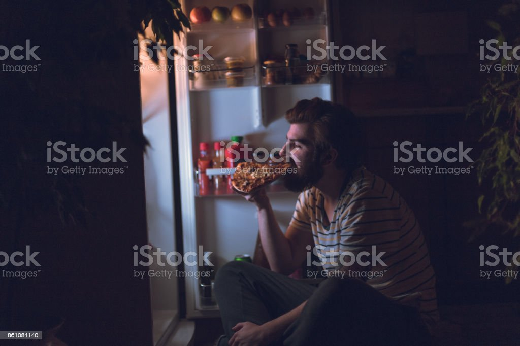 Handsome man eating pizza late night stock photo