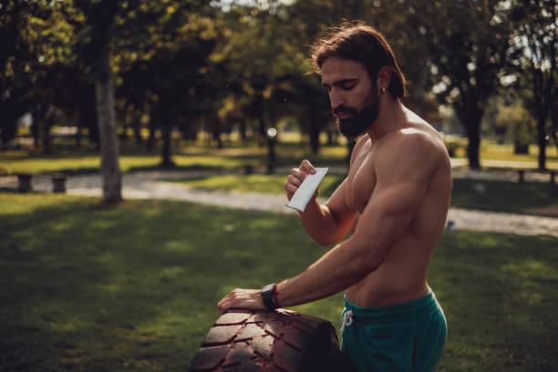 Hombre guapo comiendo barra de proteínas después de un entrenamiento duro - foto de stock
