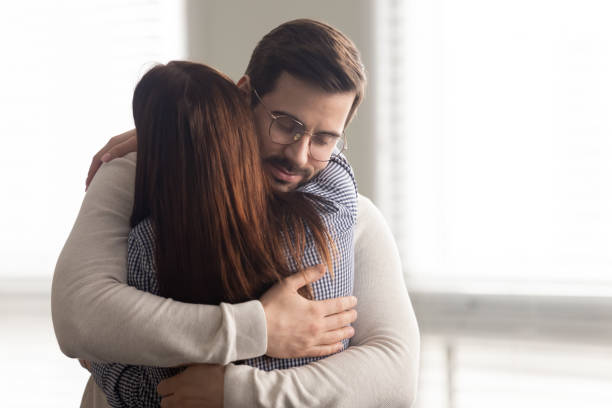 Handsome man embracing woman calms in difficult moment. stock photo
