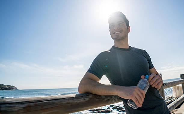 handsome man exercising outdoors - wasser trinken abnehmen stock-fotos und bilder