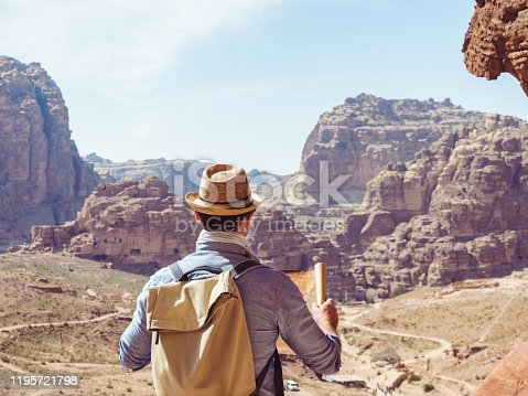 Handsome man, exploring the sights of the ancient, fabulous city of Petra in Jordan. Colorful photos. Concept of leisure, vacation and travel