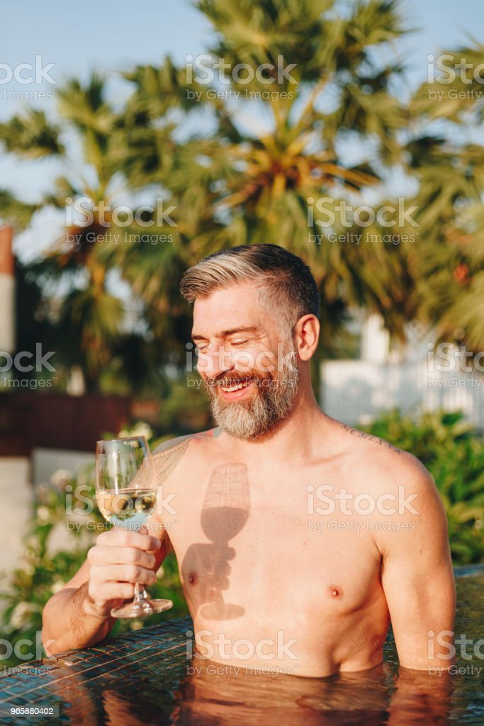 Handsome man having a glass of wine in the pool - Royalty-free Adult Stock Photo