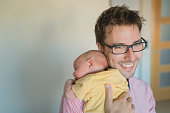 Handsome man holding a newborn baby in her arms. Paternity concept.