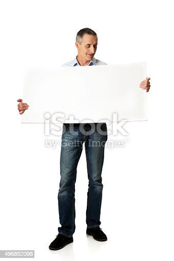 istock Handsome man holding an empty banner 496852098