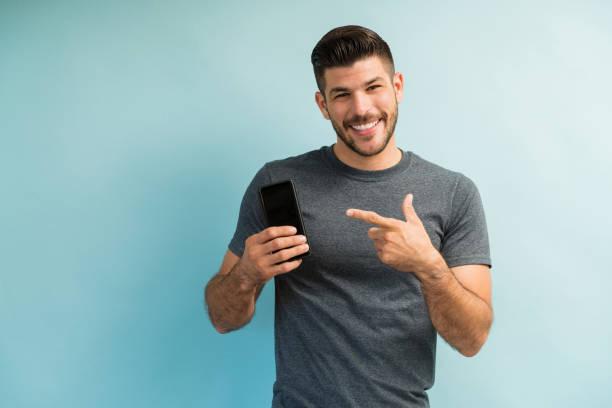 Handsome Man Holding Smartphone vor dem hintergrund – Foto