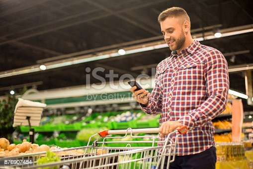 istock Handsome Man Holding Smartphone in Supermarket 876907484