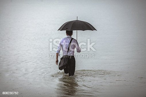 istock Handsome man holding umbrella walks through the water during rain 606230752