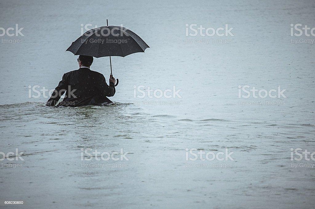 Handsome man holding umbrella walks through the water during rain stock photo