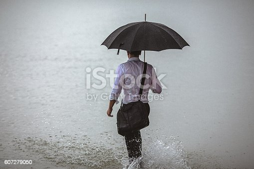 istock Handsome man holding umbrella walks through the water during rain 607279050