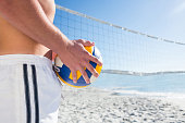 Handsome man holding volleyball at the beach