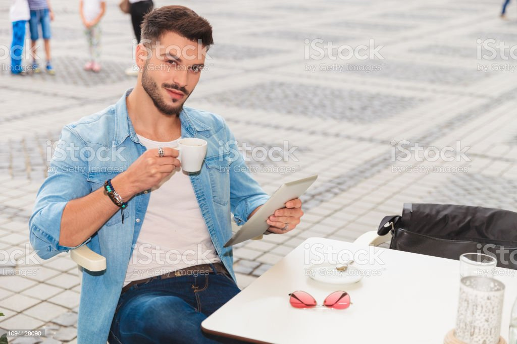 handsome man holds tablet while taking coffee break in the city and...