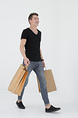 man walking with lots of shopping bags isolated on white background.