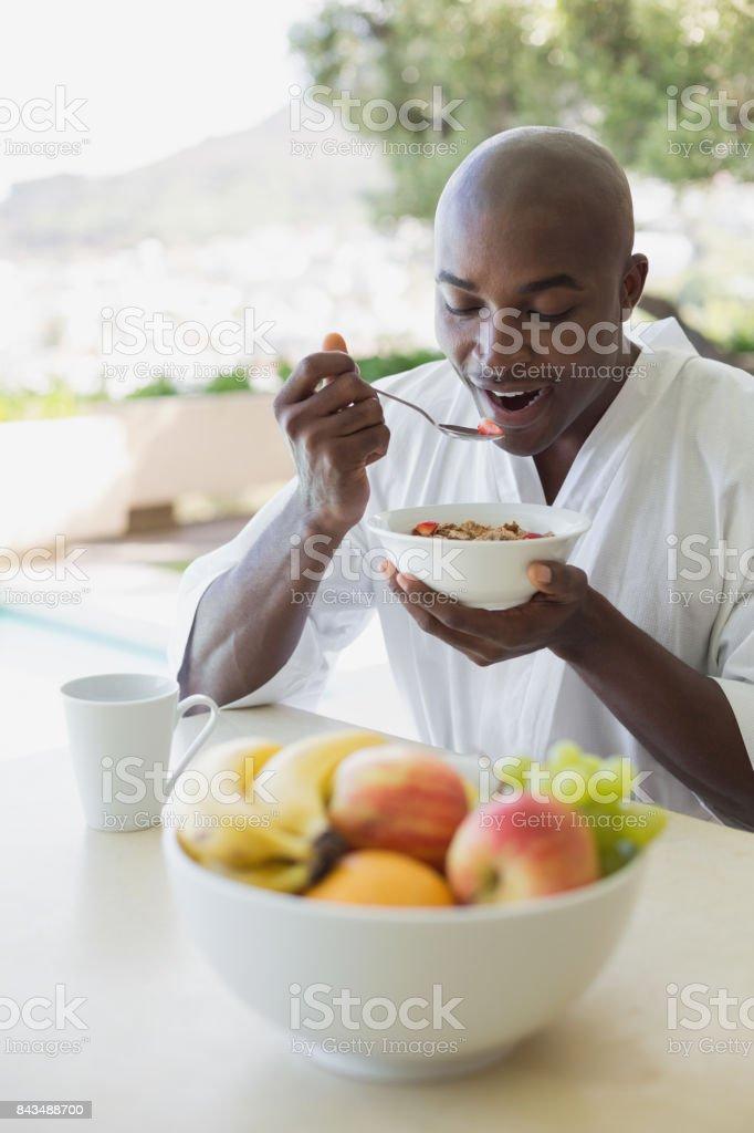 Handsome man in bathrobe having breakfast outside stock photo