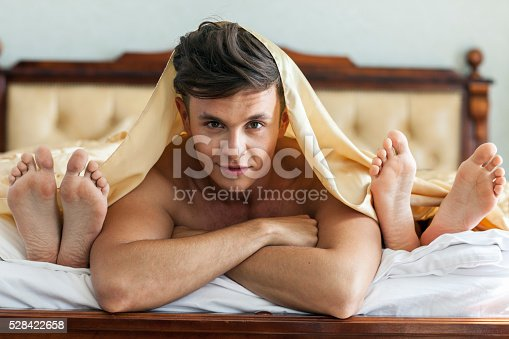 istock Handsome Man In Bed With Two Women 528422658