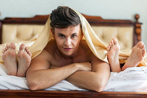 handsome man in bed with two women - three people stock photos and pictures