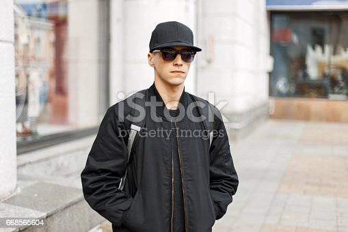 istock Handsome man in black glasses and a baseball cap, a black fashionable jacket walks around the city 668565604