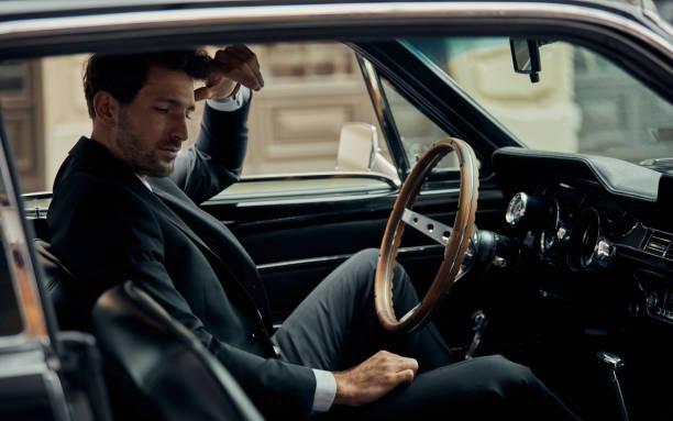 hübscher mann im schwarzen anzug im alten oldtimer - 1m coupe stock-fotos und bilder