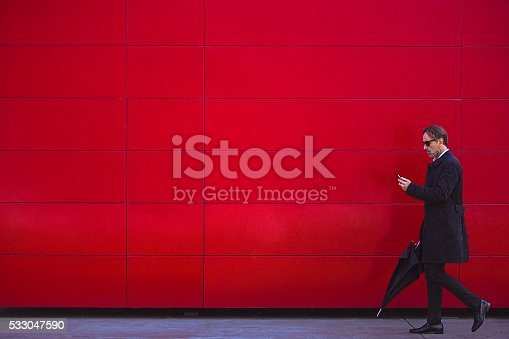 Handsome mature man wearing black clothes, black sunglasses and black umbrella, walking beside the red wall and and watching photographs on Getty images mobile application on his smartphone. Full length, copy space.