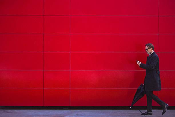 homem bonito em preto caminhar ao lado da parede vermelha - homem chapéu imagens e fotografias de stock