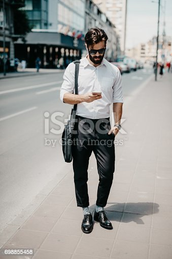 istock Handsome man in businesswear is texting for uber 698855458