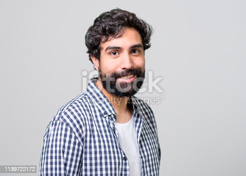 Side view of handsome man wearing checked shirt. Portrait of confident male is smiling. He is standing over gray background.