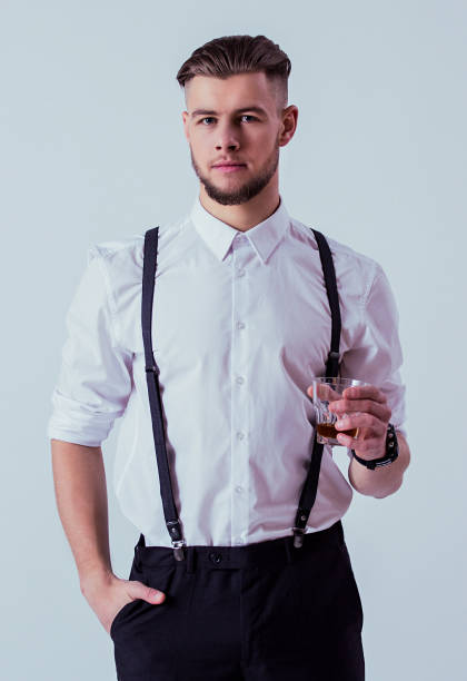 Handsome man in classical wear drinking whiskey in studio Confident and elegant man in classical wear keeping hand in pocket and looking to camera while drinking whiskey or scotch against gray background. Men with glass of alcohol. Masculinity and charisma suspenders stock pictures, royalty-free photos & images
