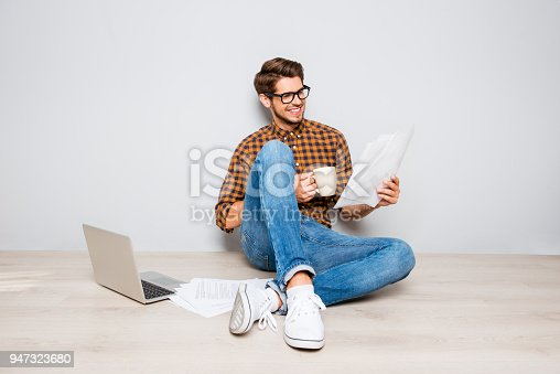 947303582 istock photo Handsome man in glasses sitting on floor and reading contract 947323680