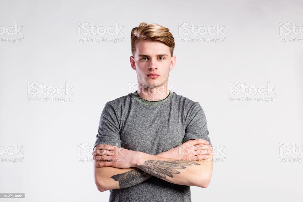Handsome man in gray t-shirt, tattoo on forearms, studio shot. stock photo