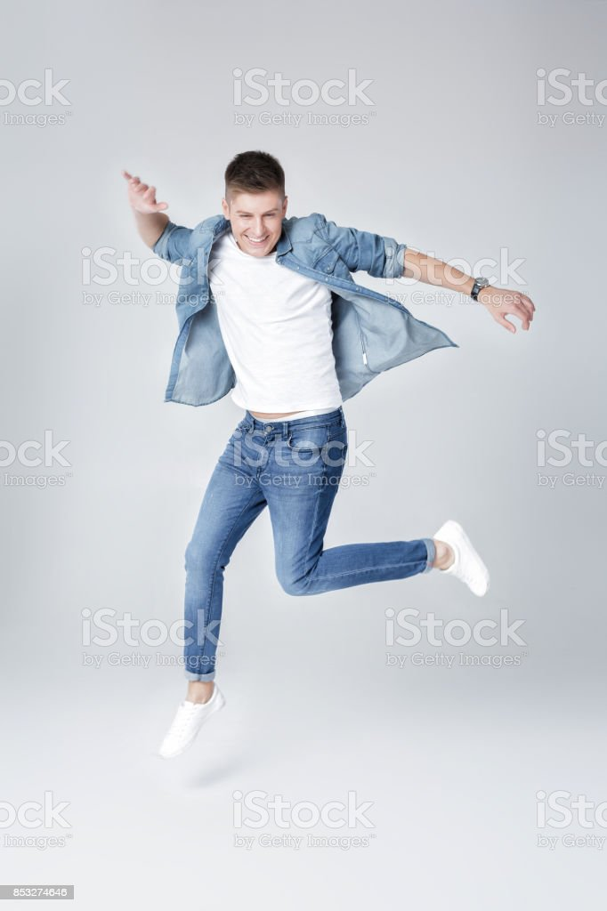 handsome man in jeans and jacket jumping stock photo